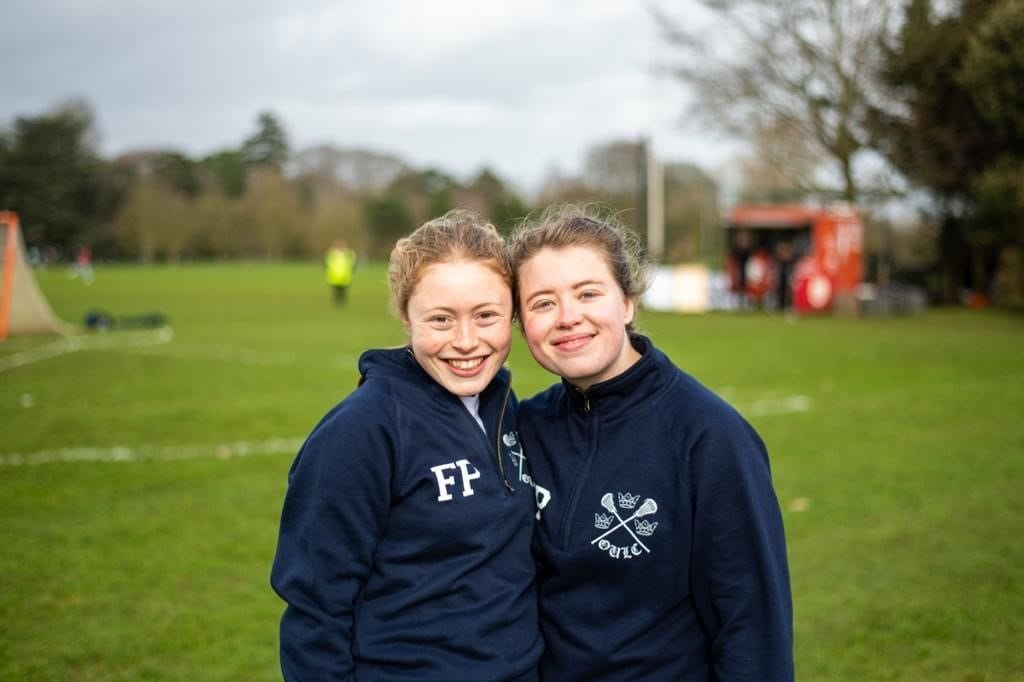 Two female members of the lacrosse team stand side by side smiling