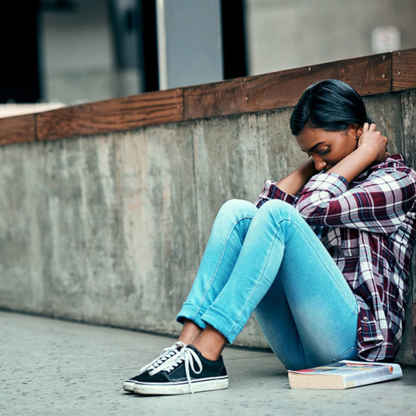 Young girl sat on the floor outside looking stressed